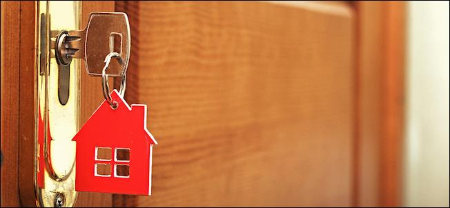 Una llave en una cerradura con el icono de la casa en i