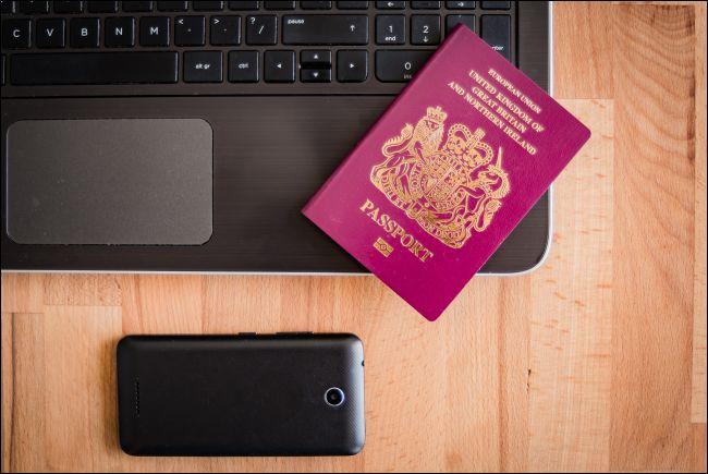 Pasaporte británico con laptop y smartphone