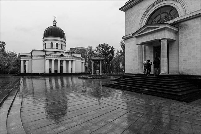 Un reflejo de un edificio en un patio de ladrillo mojado en una foto en blanco y negro.