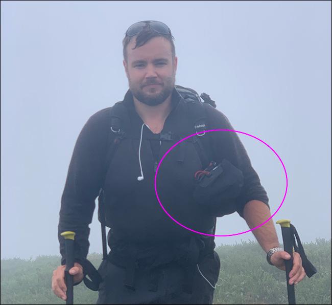 Un hombre que camina bajo la lluvia con un trípode y una bolsa Peak Design Camera Shell.