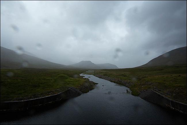 Una foto lluviosa de una montaña y un arroyo con gotas de agua en la lente.