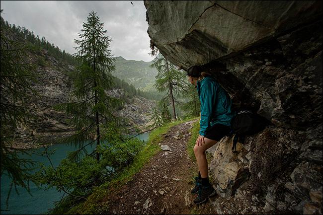 Una mujer resguardada de la lluvia bajo un acantilado en las montañas.