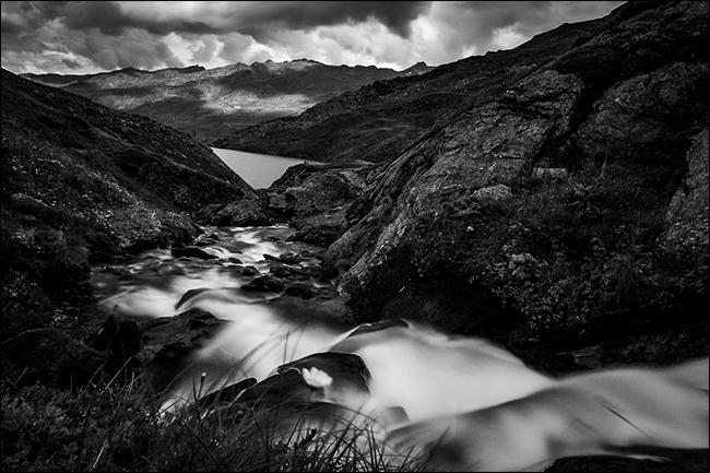 Una fotografía en blanco y negro de un arroyo en las montañas después de que llovió.