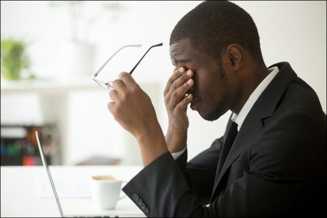 Un hombre sentado frente a su computadora portátil, sosteniendo sus lentes y frotándose los ojos.