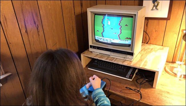 Un niño jugando River Raid en una computadora Atari 800XL.
