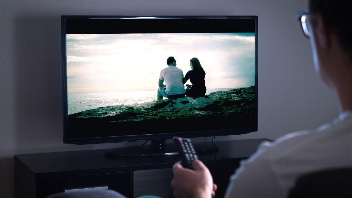 Hombre apuntando a TV remota