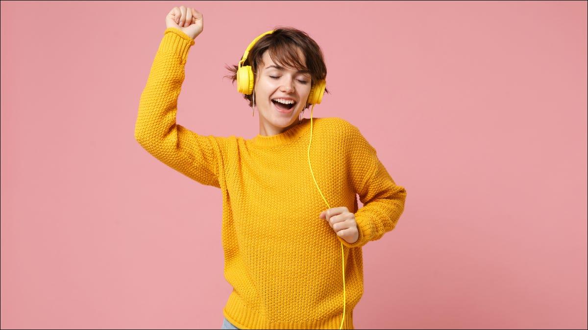 Mujer en suéter amarillo bailando mientras escucha música en auriculares amarillos con cable