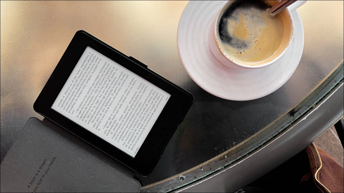 Kindle acostado sobre una tableta junto a una taza de café