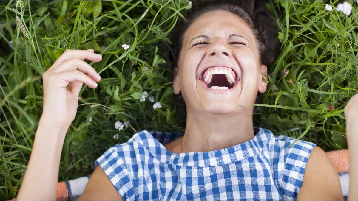 Mujer rodando sobre la hierba riendo.
